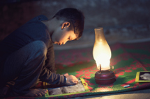 Child working by lantern light