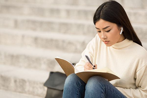 Asian woman listening to earbuds and writing in a notebook while sitting on steps