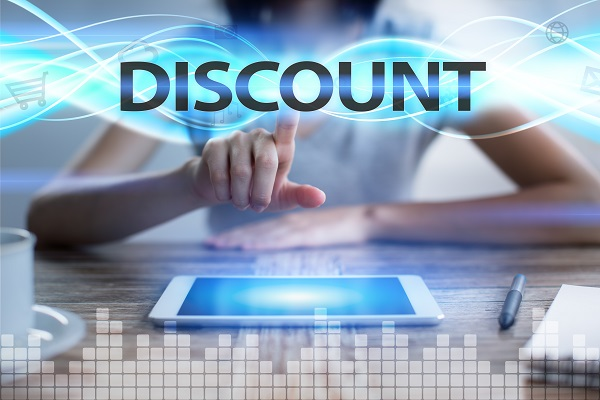 "A person is tapping on a tablet sitting on a desk. The word ""DISCOUNT"" is at the top."