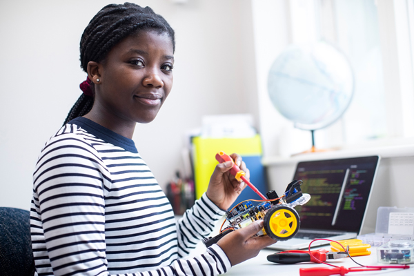Young Black woman using tools at desk in front of computer screen