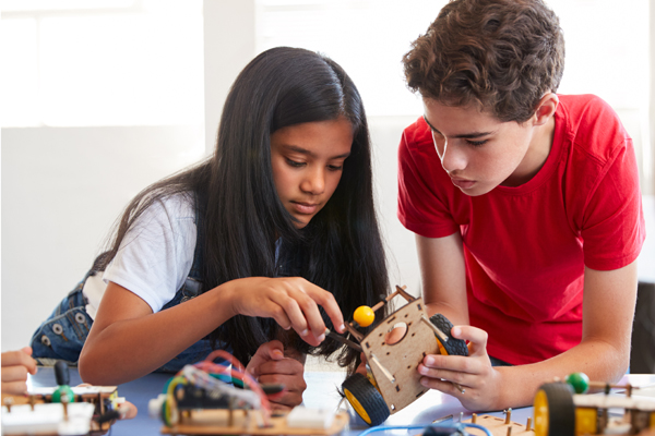 A girl and boy tinkering with a STEM project in a bright room
