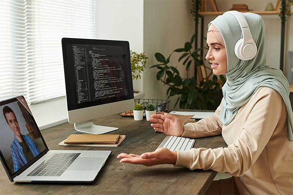 Woman wearing hijab and headphones on conference call on laptop, with second monitor in background